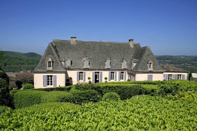 Oud huis in gemodelleerde tuin royalty-vrije stock afbeelding