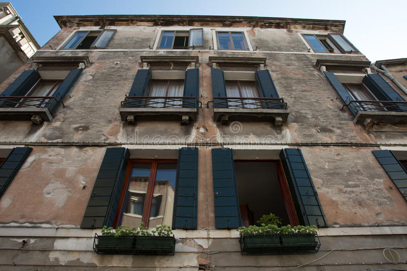 Oud huis met blinden verfraaide bloempotten royalty-vrije stock afbeelding