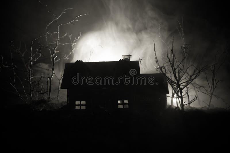 Oud huis met een Spook in het bos bij nacht of Verlaten Achtervolgd Verschrikkingshuis in mist De oude mysticusbouw in dood boomb royalty-vrije stock fotografie
