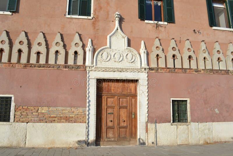 Oud huis met enorme houten hoofddeur bij de Italiaanse strandboulevard van Venetië van de lagune van Venetië royalty-vrije stock afbeeldingen