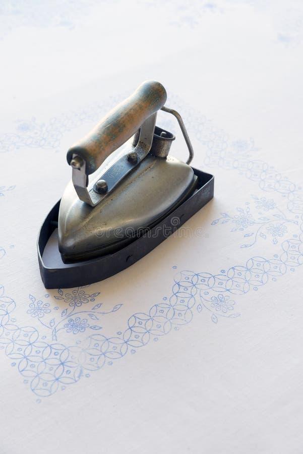 Oud ijzer op een geborduurd tafelkleed stock afbeelding