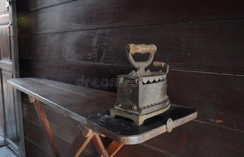 Oud Ijzer op uitstekende strijkplank stock foto's