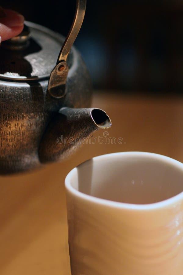 Oud ijzervee klaar om thee in een kop te gieten stock afbeeldingen