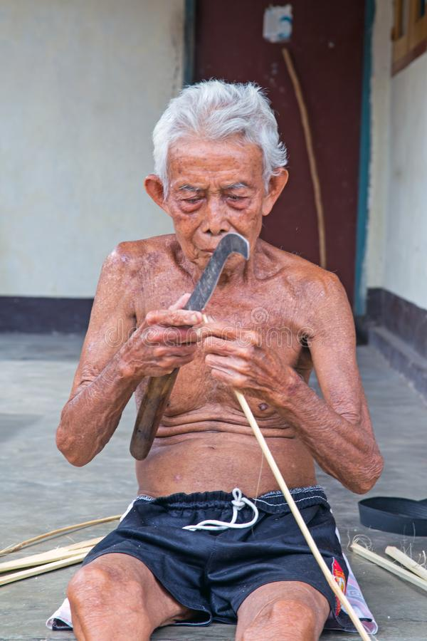 Oud Indonesisch mensen scherp gras in Lombok, Indonesië stock foto's