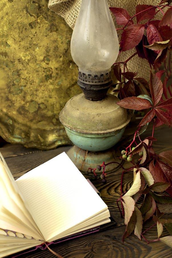 Oud kerosinelamp en dienblad, open notitieboekje en rode bladeren van druiven op een houten lijst in rustieke stijl stock afbeeldingen