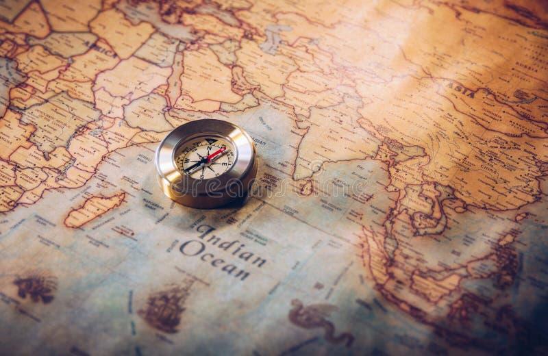 Oud kompas op uitstekende kaart De achtergrond van avonturenverhalen stock afbeeldingen