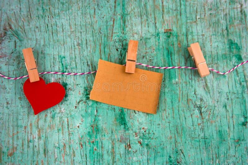 Oud leeg document en document rood die hart op wasknijpers wordt gehangen stock fotografie