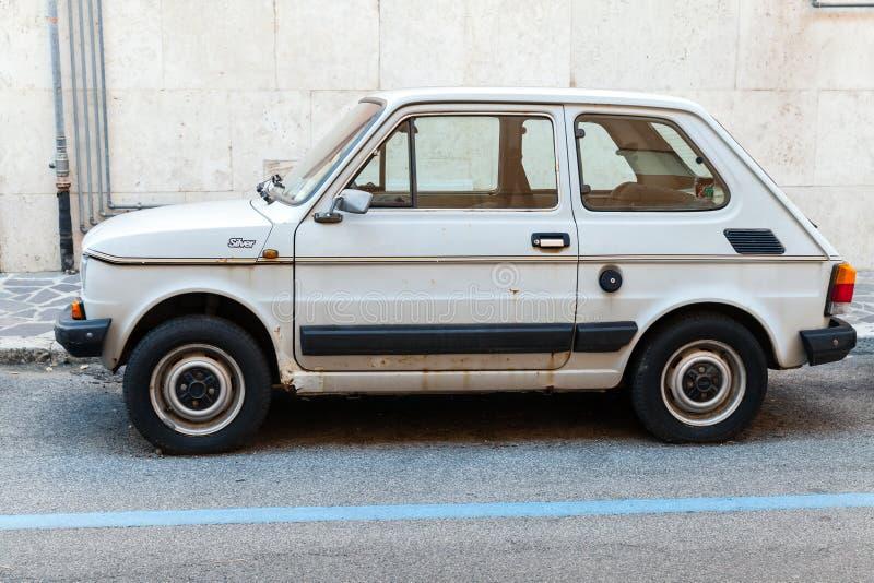 Oud lichtgrijs die Fiat 126 op een kant van de weg wordt geparkeerd stock afbeelding