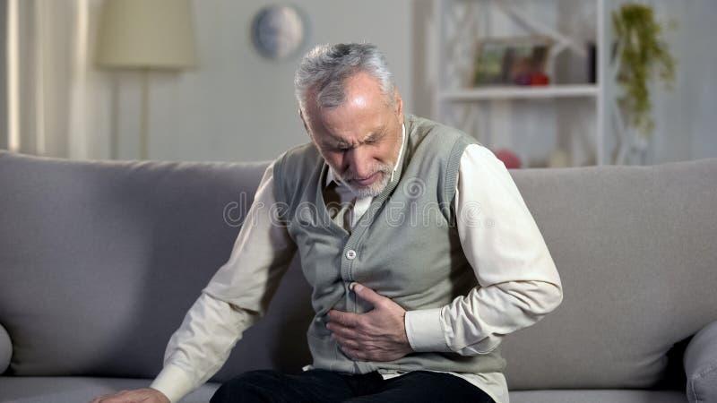 Oud mannetje die sterke buikpijn, maagzweerziekte hebben, gezondheidsproblemen stock afbeeldingen