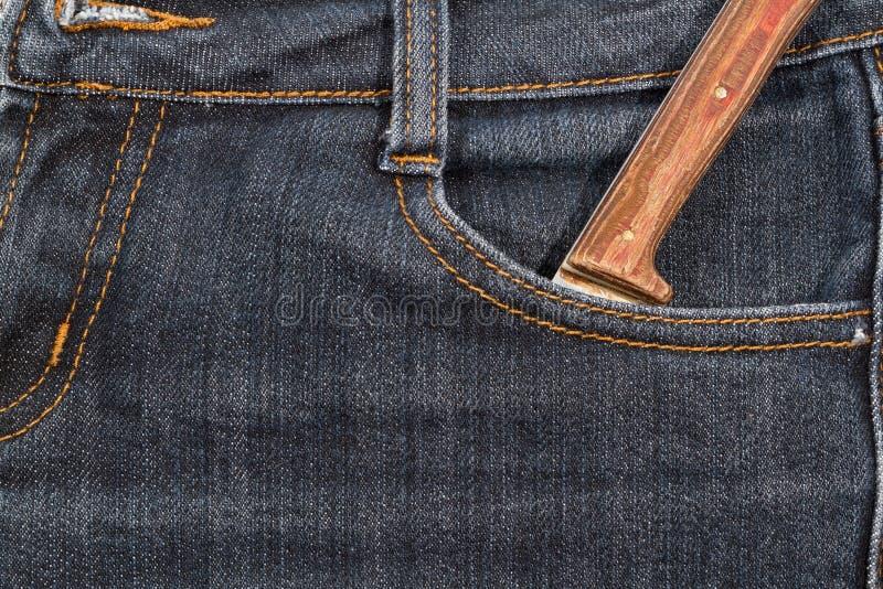 Oud mes met een houten handvat in uw zakjeans stock afbeelding