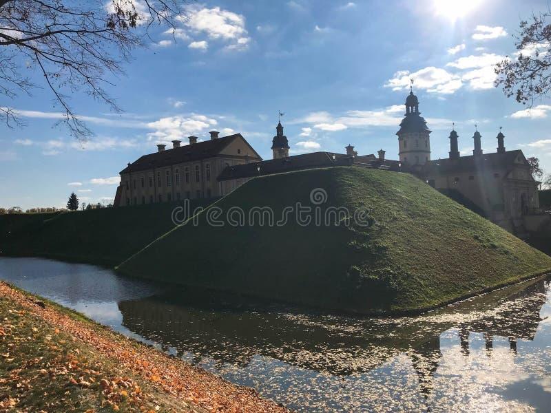 Oud, oud middeleeuws die kasteel met spiers en torens, muren van steen en baksteen door een beschermende gracht met water wordt o stock fotografie