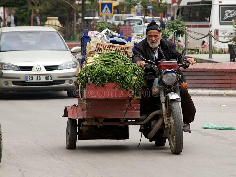 Oud ontmoet nieuw op de straten van Turkse stad. Kruidenier die zijn groenten vervoeren aan bazaarmarkt. stock foto's