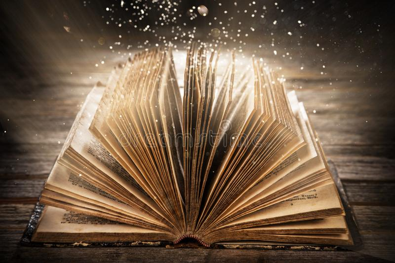 Oud open boek op houten lijst met mysticus magisch helder licht stock afbeelding