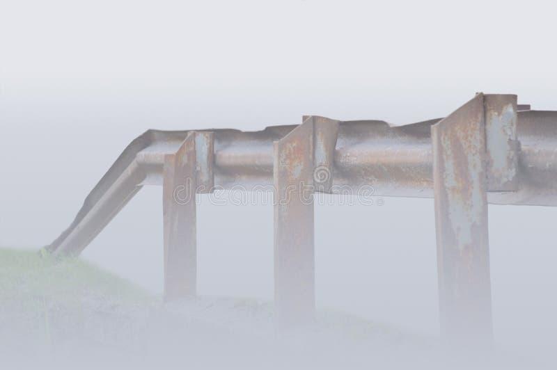 Oud oud roestig het spoorperspectief van de grunge metaaldiebrug, in Schotse mist wordt gehuld, grijze blauwe close-up royalty-vrije stock foto's