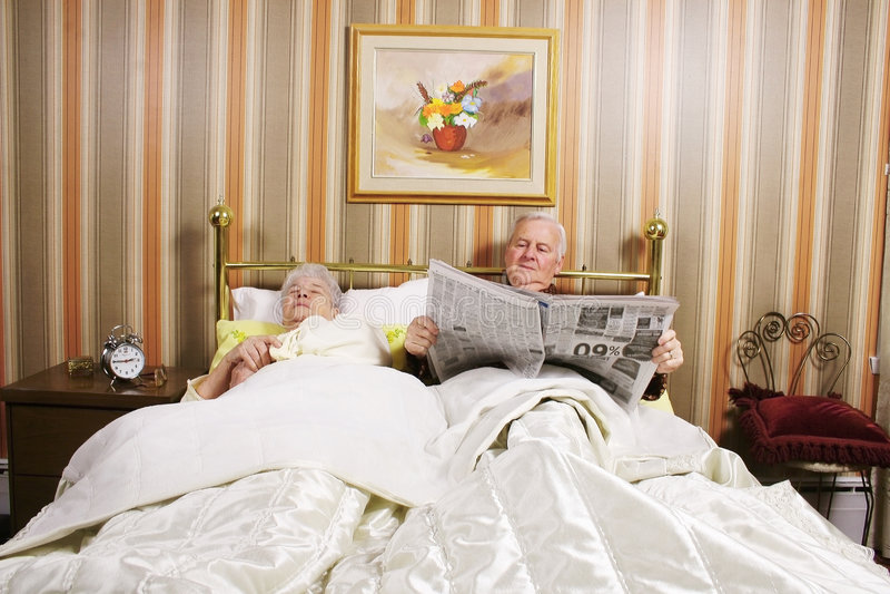 Oud paar in bed stock afbeelding