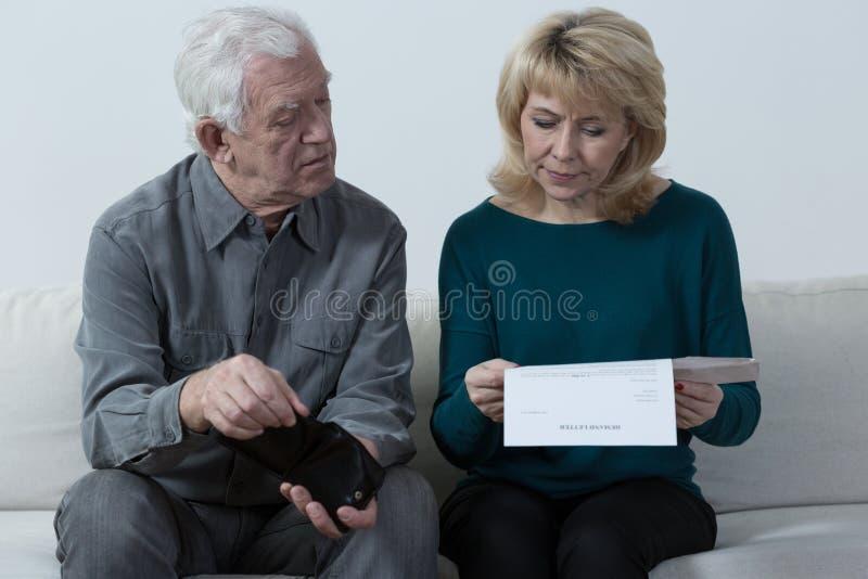 Oud paar die onbetaalde rekeningen analyseren royalty-vrije stock afbeeldingen