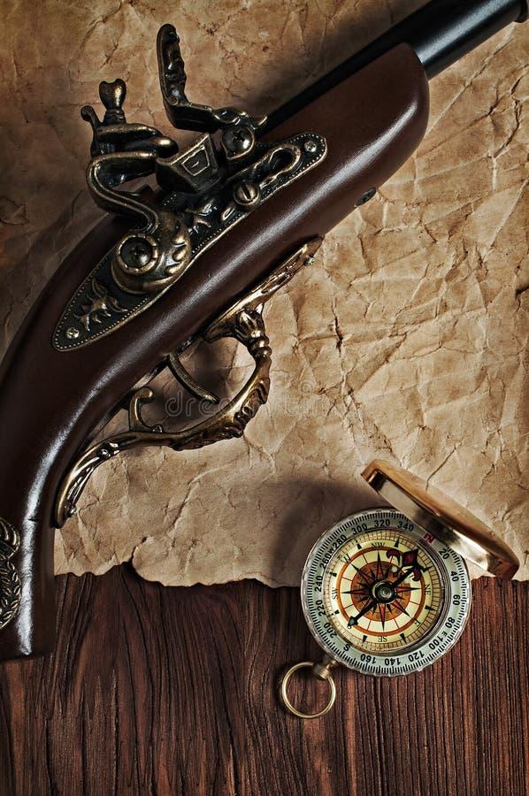 Oud pistool en messingskompas stock afbeeldingen