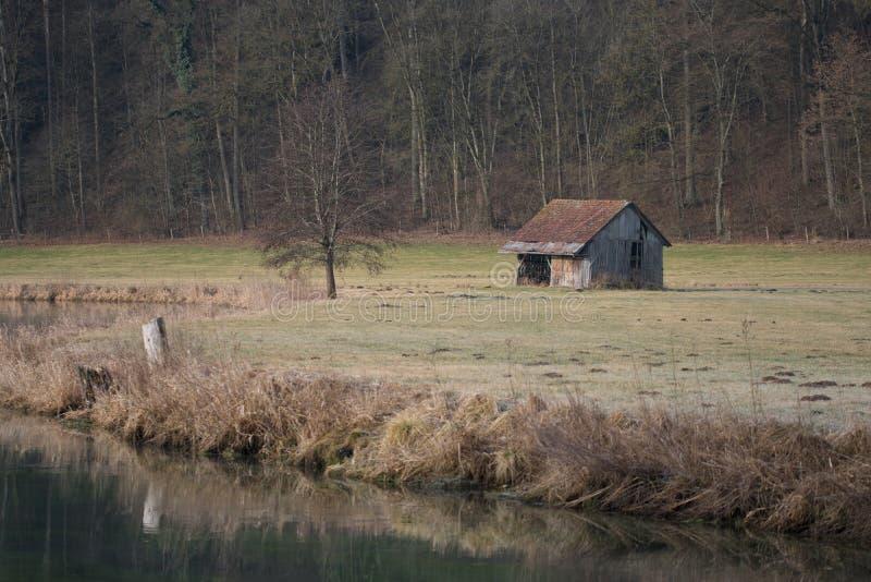 Oud plattelandshuisje door de rivier en het bos stock afbeelding