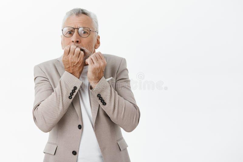 Oud rijke man doen schrikken het verliezen geld Portret van zenuwachtig bang hoger mannelijk model in glazen en kostuum het bijte stock afbeeldingen