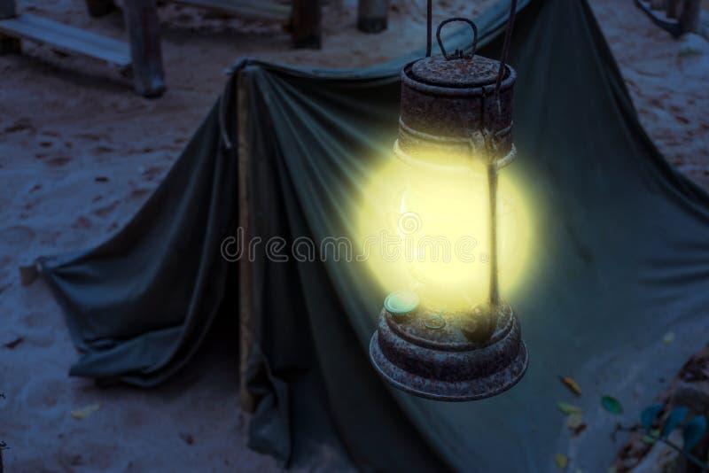 Oud roestig Aangestoken lantaarn het glanzen helder licht tijdens nacht, Mijnwerkerskamp, Overlevingsstijging in 's nachts aard stock foto's