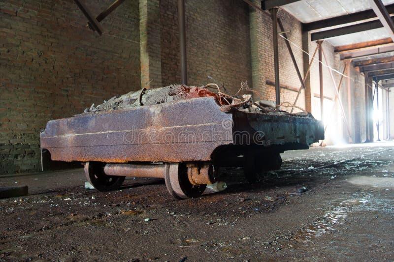 Oud roestig karretje in verlaten fabriek royalty-vrije stock fotografie