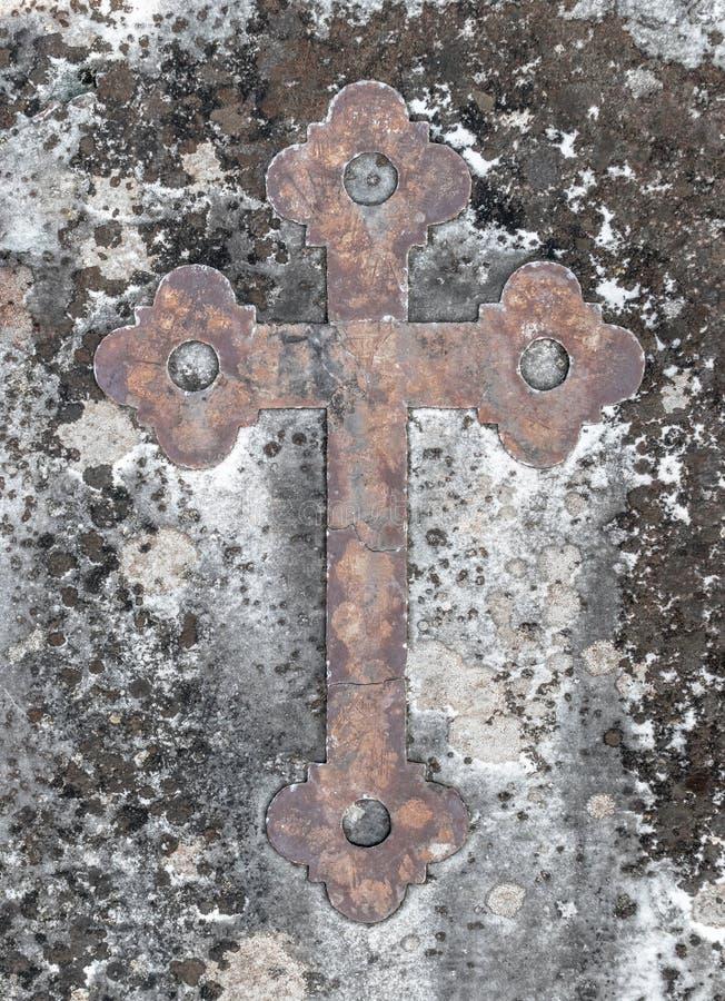 Oud roestig kruis op een oude steen stock foto's