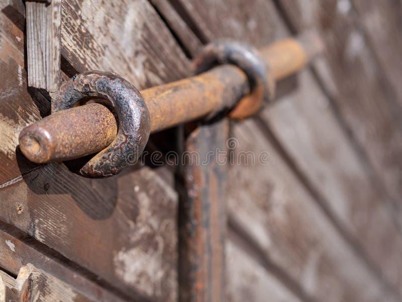 Oud roestig metaal deadbolt op een houten deur stock foto's