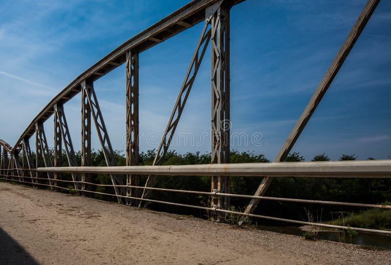 Oud roestig metaaltraliewerk op de brug Weg met gebarsten asphal stock fotografie