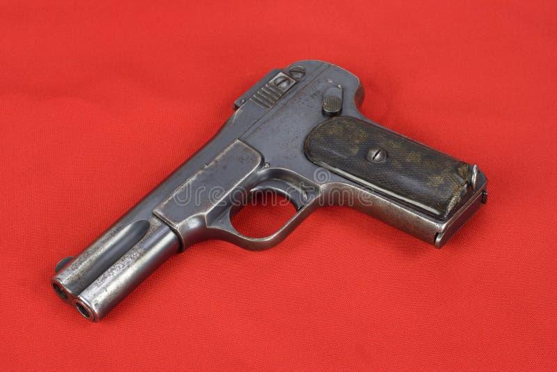 Oud roestig pistool op rood stock foto's
