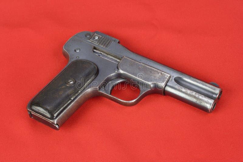 Oud roestig pistool op rood royalty-vrije stock fotografie
