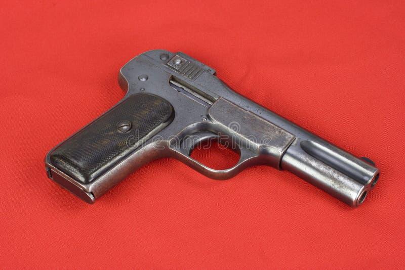 Oud roestig pistool op rood royalty-vrije stock afbeelding
