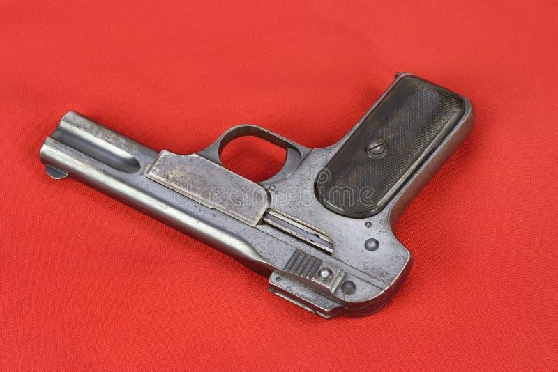Oud roestig pistool op rood royalty-vrije stock afbeeldingen