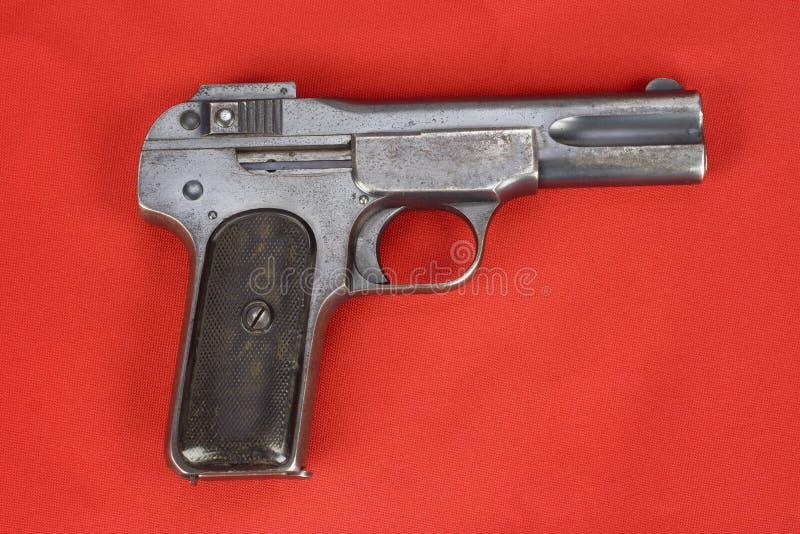 Oud roestig pistool op rood stock foto