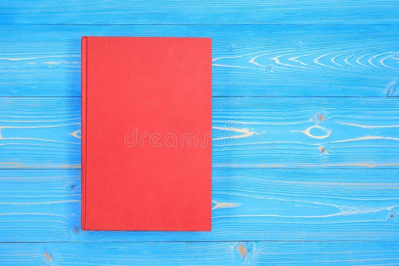 Oud rood boek op houten plankachtergrond Lege lege dekking voor D stock fotografie