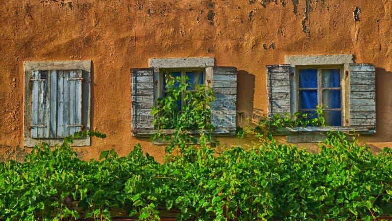 Oud rustiek huis met een nadruk op houten vensters stock afbeeldingen
