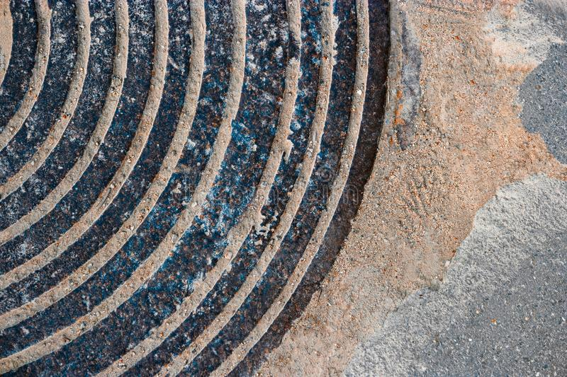 Oud Rusty Manhole Cover Circular Pattern met Zand of Vuil op The Edge stock foto
