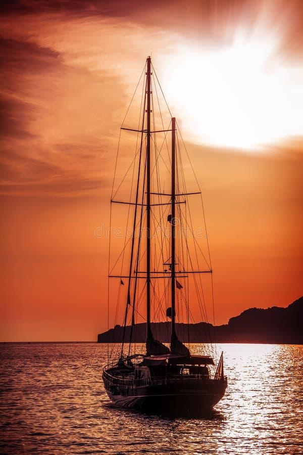 Oud schip die aan de zonsondergang varen stock fotografie