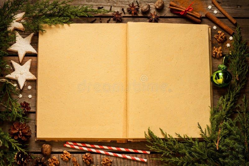 Oud spatie geopend boek met Kerstmisdecoratie rond op hout royalty-vrije stock afbeeldingen