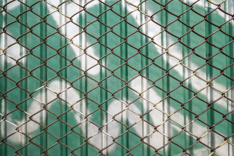 Oud staal netto met groene zinkmuur royalty-vrije stock foto's