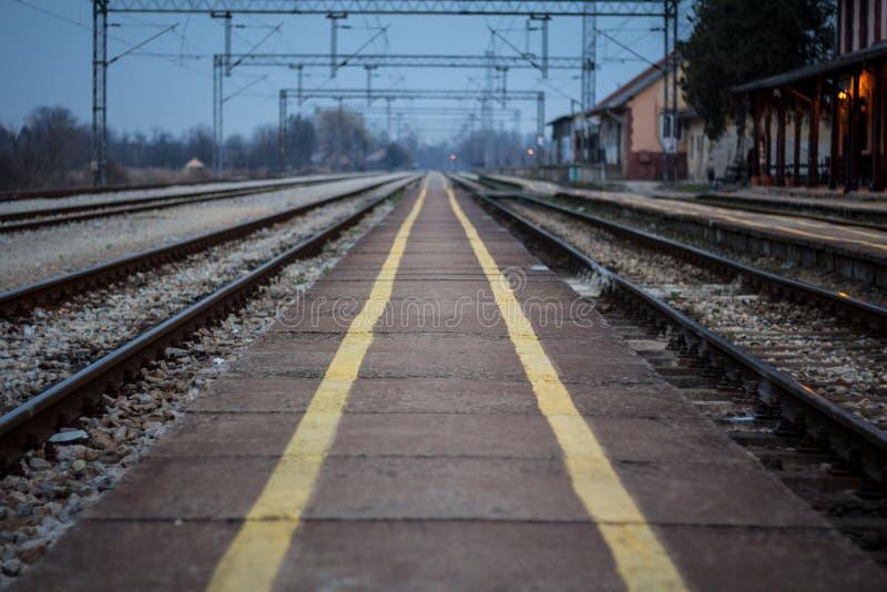 Oud stationplatform met zijn distinctieve gele veiligheidslijnen op een bijna verlaten geëlektriseerde spoorlijn bij zonsondergan royalty-vrije stock foto's