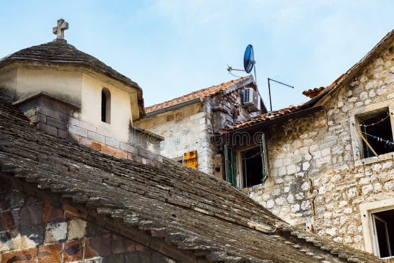Oud steenhuis in een slechte buurt, die zich naast een kleine oude kerk bevinden stock foto