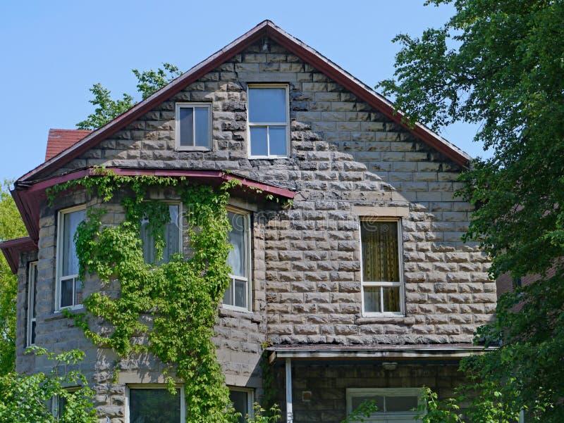 Oud steenhuis met geveltop en wijnstokken royalty-vrije stock afbeelding