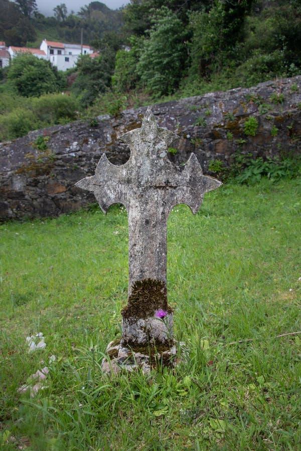 Oud steenkruis van een grafzerk in een landelijk begraafplaatshoogtepunt van gras in Galici?, Spanje royalty-vrije stock afbeeldingen