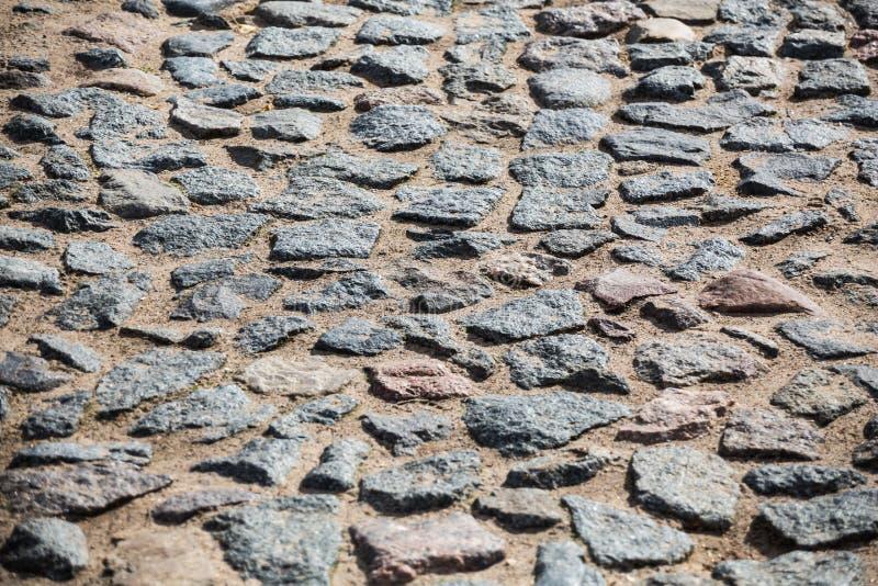 Oud steenwegdek Bestrating Keien en zand stock afbeeldingen