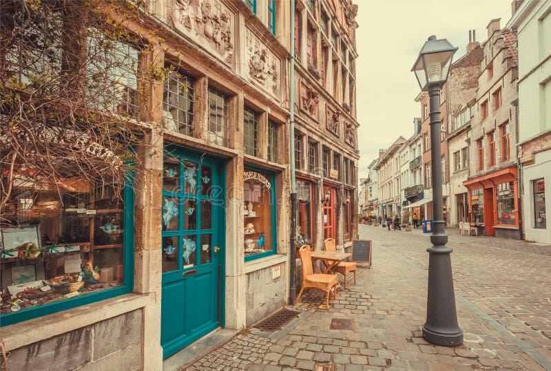 Oud straatlantaarn en baksteenhuis met hulp op muur en kleine opslag met kleurrijke deuren stock foto's