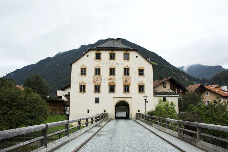 Oud torenhuis en oude brug over Slechte herbergenrivier bij Pfunds-dorp, Oostenrijk stock foto