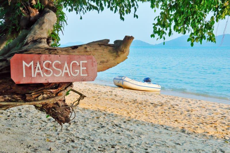 Oud uithangbord met inschrijving, massage, op een tropisch strand stock afbeeldingen