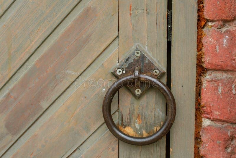 Oud uitstekend deurhandvat op een houten deur stock fotografie
