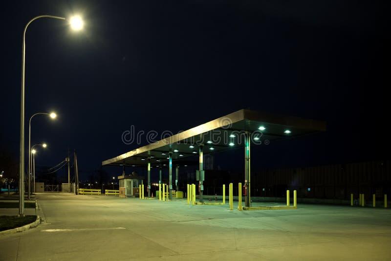 Oud uitstekend industrieel benzinestation bij nacht stock fotografie