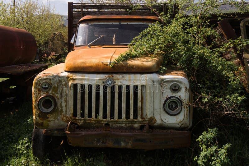 Oud uitstekend overwoekerd vrachtwagenwrak royalty-vrije stock afbeelding